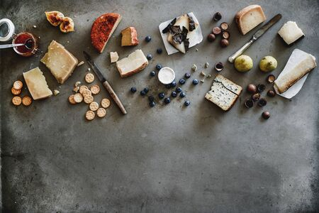 Wine snack variety. Flat-lay of cheeses, jam, fresh fruit, nuts and crackers over rough grey concrete background, top view, copy space. Gathering, party, holiday food concept