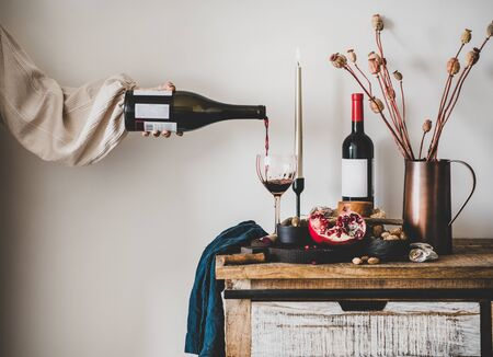Red wine, board with cheese, fruit, almonds and olives, candles, decorative flowers on kitchen counter and womans hand pouring wine to glass, white wall at background. Winery, wine tasting concept Banco de Imagens