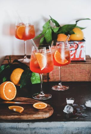 Aperol Spritz aperitif alcohol cold drink in glasses with oranges and ice cubes on concrete table, white background. Summer refreshing drink concept