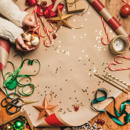Preparing for New Year. Flat-lay of hot chocolate in mug in womans hands, candy canes, Christmas ribbons, wreath, glittering balls over gift paper background, top view, copy space, square crop