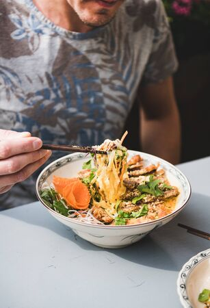 Man having dinner at vietnamese restaurant. Young man eating vietnamese noodle curry with duck with bamboo chopsticks from beautiful Asian porcelain plate. Asian, oriental fastfood cuisine