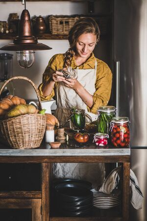Autumn vegetable pickling and canning. Young blond woman in linen apron adding pepper to cucumbers and cooking homemade vegetables preserves in kitchen. Healthy organic fermented food concept