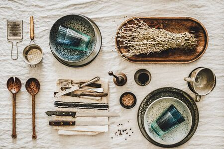 Flat-lay of various kitchen utensils, rustic tablewear, plates, dishes, glasswear, textile for cooking food over white rustic linen tablecloth background, top view. Seasonal cooking