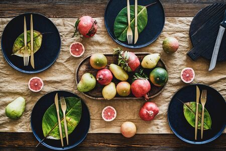 Fall or Autumn table styling for holiday dinner. Flat-lay of black dinnerware with fruit and fallen leaves for decoration over wooden table, top view. Preparing for Thanksgiving day or Christmas