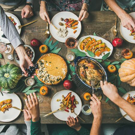 Thanksgiving, Friendsgiving holiday celebration. Flat-lay of friends eating meals at Thanksgiving Day table with turkey, pumpkin pie, roasted vegetables, fruit, rose wine, top view, square crop Banco de Imagens
