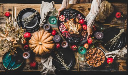 Thanksgiving party table setting for gathering. Flat-lay of roasted chicken, vegetables, fig pie, Autumn fruit, pumpkin, candles, tableware, silverware over rustic wooden table background, top view Banco de Imagens - 131489653