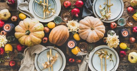 Fall table setting for Thanksgiving day or family dinner. Flat-lay plates, silverware, floral and fruit decoration, candle and pumpkins over rustic wooden table background, top view, wide composition Banco de Imagens