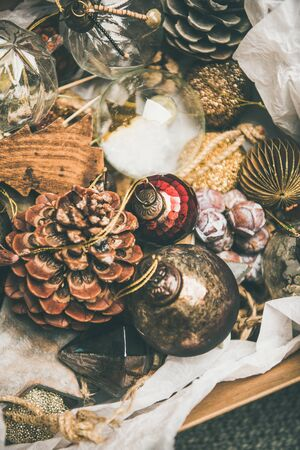 Christmas or New Year preparations. Various vintage Christmas tree decoration toys and pine cones in box, top view, selective focus. Festive holiday mood Banco de Imagens - 131833989