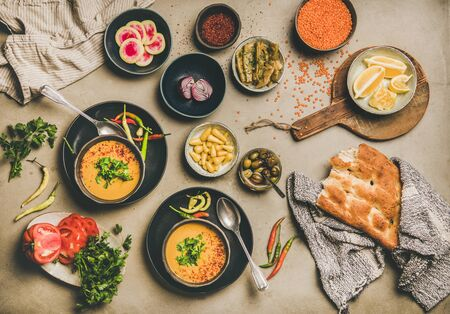 Turkish lentil soup Mercimek. Flat-lay of yellow soup, vegetables, flatbread, pickled peppers, beans, greens and spices over concrete background, top view. Vegetarian, Oriental, Middle Eastern cuisine Banco de Imagens