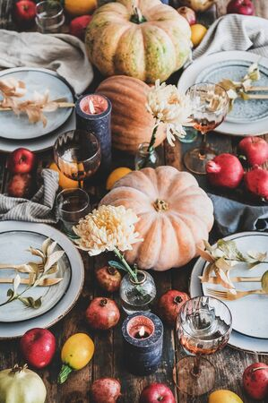 Fall table setting for Thanksgiving day or family gathering dinner. Plates, silverware, floral and fruits decoration, candles and pumpkins over rustic wooden table background