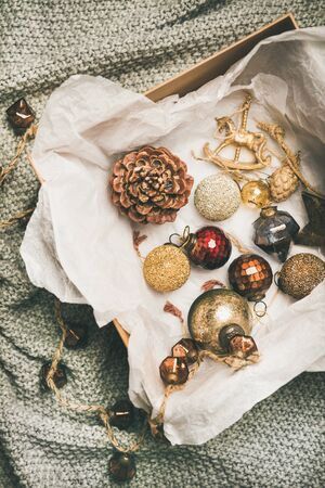 Christmas or New Year preparations. Flat-lay of various vintage Christmas tree decoration toys, balls, garland and pine cones in wooden box over grey knitted background, top view. Festive holiday mood