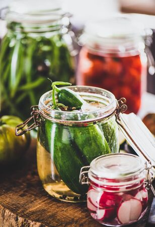 Autumn vegetable pickling and canning. Ingredients for cooking and glass jars with homemade vegetables preserves on rustic wooden table, close-up. Healthy organic fermented food concept Banco de Imagens
