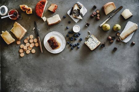 Wine snack variety. Flat-lay of cheeses, honey, fresh fruit, nuts and crackers over rough grey concrete background, top view, copy space. Gathering, party, holiday food concept