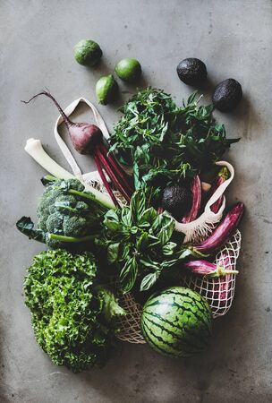 Healthy grocery goods. Flat-lay of net bag full of vegetables, fruits, greens from local farmers market over concrete kitchen counter, top view. Eco-friendly, zero waste, clean eating, vegan concept