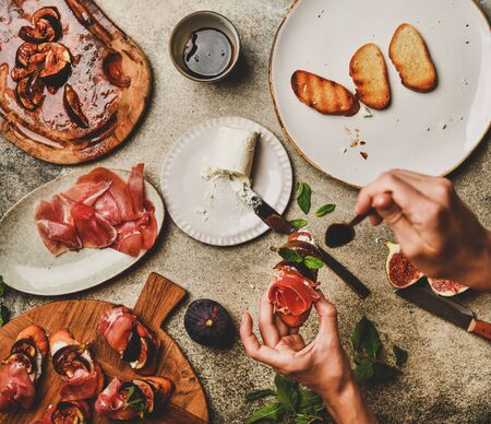 Party or catering food cooking. Flat-lay of crostini with prosciutto, grilled figs, goat cheese and female hands with canape over grey concrete table background, top view