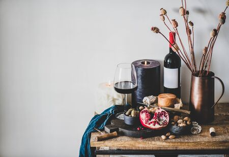 Wine and snack set. Glass and bottle of red wine, serving board with cheese, fruit, nut and olives, candles on kitchen counter, white wall background, copy space. Wine tasting, winebar, winery concept