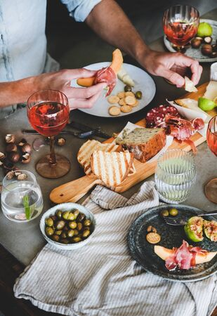 Mid-summer picnic with wine and snacks. Charcuterie and cheese board, rose wine, nuts, olives, fresh fruits and mans hands with food over concrete table background, top view Banco de Imagens
