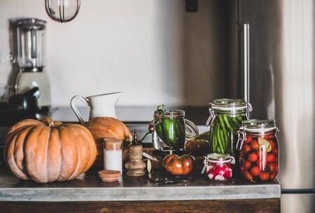 Autumn vegetable pickling and canning. Ingredients for cooking and glass jars with homemade vegetables preserves on kitchen counter, close-up. Healthy organic fermented food concept Banco de Imagens