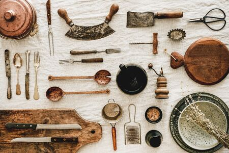 Flat-lay of various kitchen utensils, rustic tablewear, wooden board for cooking, plates, dishes, glasswear, scissors, corkscrew over white linen tablecloth background, top view