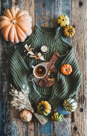 Autumn outfit layout. Flat-lay of dark green knitted sweater, blue jeans, hat, decorative pumpkins, candle, accessories and tea in cup on board over wooden background, top view. Fall apparel and mood Banco de Imagens