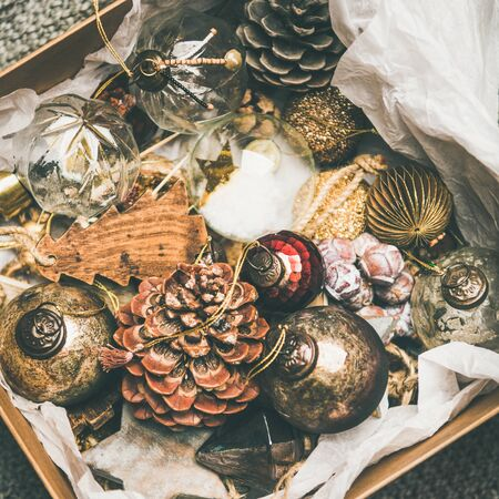 Christmas or New Year preparations. Flat-lay of various vintage Christmas tree decoration toys and pine cones in wooden box over grey floor background, top view, square crop. Festive holiday mood
