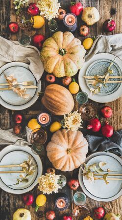 Fall table setting for Thanksgiving day or family gathering dinner. Flat-lay of plates, silverware, floral and fresh fruit decoration, candle and pumpkins over rustic wooden table background, top view Banco de Imagens