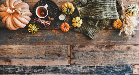 Autumn outfit layout. Flat-lay of dark green knitted sweater, blue jeans, hat, decorative pumpkins, candle, accessories and tea in cup on board over wooden background, top view, copy space