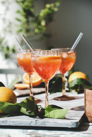 Aperol Spritz aperitif alcohol cold drink in glasses with oranges and ice over grey marble board, selective focus. Summer refreshing drink concept 스톡 콘텐츠