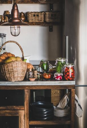 Autumn vegetable pickling and canning. Fresh ingredients and glass jars with homemade vegetables preserves on kitchen counter. Healthy organic fermented food concept