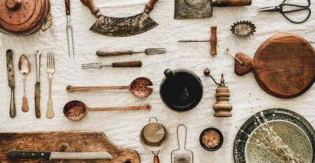 Flat-lay of various kitchen utensils, rustic tablewear, wooden board for cooking, plates, dishes, glasswear, scissors, corkscrew over white linen tablecloth background, top view, wide composition
