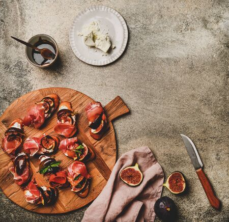 Party or catering food. Flat-lay of crostini with prosciutto, goat cheese and grilled figs and ingredients for making over grey concrete table background, top view, copy space