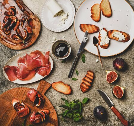 Party or catering food cooking. Flat-lay of crostini with prosciutto, goat cheese and grilled figs and ingredients over grey concrete table background, top view