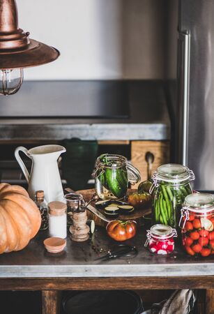 Autumn vegetable pickling and canning. Ingredients for cooking and glass jars with homemade vegetables preserves on wooden kitchen counter, close-up. Healthy organic fermented food concept