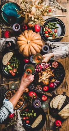Thanksgiving table setting. Flat-lay of couple celebrating holiday with champagne at festive table with roasted chicken, vegetables, fig pie, fruit, candles over wooden table background, top view
