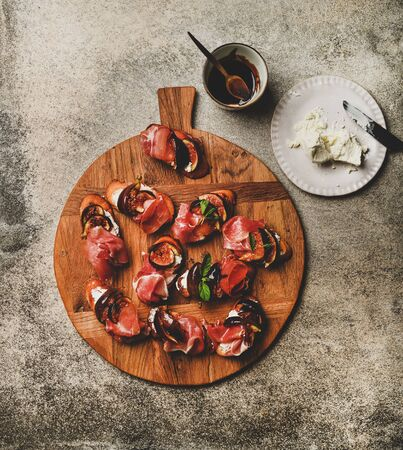 Party or catering food. Flat-lay of crostini with prosciutto, goat cheese and grilled figs on wooden board and ingredients for making over grey concrete table background, top view