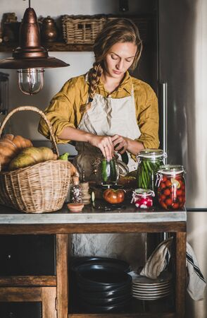 Autumn seasonal vegetable pickling and canning. Young blond woman in linen apron putting cucumbers to jar and cooking homemade vegetables preserves in kitchen. Healthy organic fermented food concept
