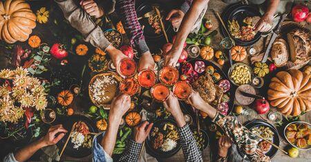 Familia celebrando el día de acción de gracias. Plano de manos de la gente del banquete tintineando vasos con vino rosado sobre la mesa de Friendsgiving con comida tradicional de otoño, pavo asado, pastel de calabaza, vista superior