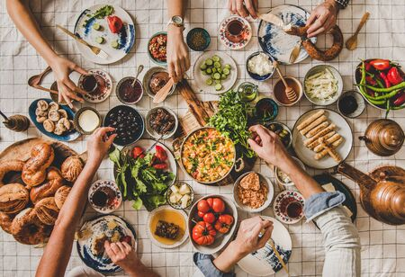 Flat-lay of family sitting at table with Turkish breakfast with pastries, vegetables, greens, spreads, cheeses, eggs, jams and tea in tulip glasses and copper teapots over chekered linen tablecloth