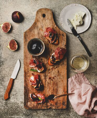 Party or catering food. Flat-lay of crostini with prosciutto, goat cheese and grilled figs on wooden board and glass of white wine over concrete background, top view