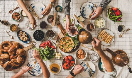Flat-lay of family having Turkish breakfast with fresh pastries, vegetables, greens, spread, cheeses, fried eggs, jams and tea in tulip glasses and copper teapots over pastel chekered linen tablecloth