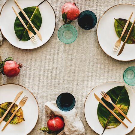Fall or Autumn table setting for holiday dinner. Flat-lay of dinnerware with fruit and leaves over linen tablecloth, top view, copy space, square crop. Preparation for Thanksgiving day or Christmas