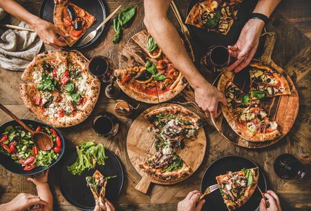 Family or friends having pizza party dinner. Flat-lay of people eating different kinds of Italian pizza, salad and drinking wine over wooden table, top view. Fast food lunch, gathering, celebration