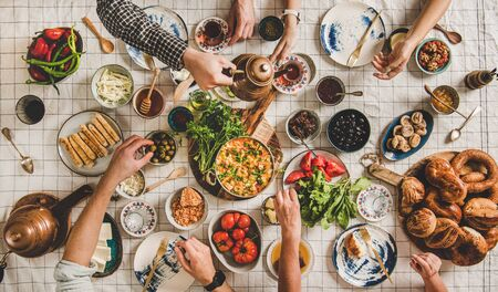 Flache Lage der Familie beim türkischen Frühstück mit Gebäck, Gemüse, Gemüse, Aufstrich, Käse, Spiegelei, Marmelade und Tee in Tulpengläsern und Kupfer-Teekannen über pastellfarbener Leinentischdecke Standard-Bild