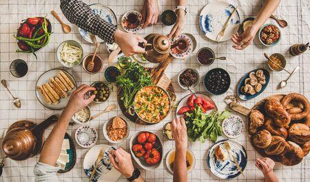 Plano de familia tomando un desayuno turco con pasteles, verduras, verduras, pastas para untar, quesos, huevos fritos, mermeladas y té en vasos de tulipán y teteras de cobre sobre un mantel de lino de cuadros en colores pastel Foto de archivo