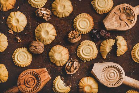 Flat-lay de galletas de sémola de Hatay tradicionales turcas con fecha, higo, relleno de nuez y moldes para hornear galletas de madera sobre fondo oscuro oxidado, vista superior. Oriente Medio cocina regional de Anatolia oriental Foto de archivo
