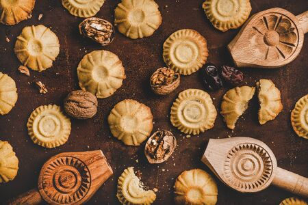Mise à plat de biscuits traditionnels turcs à la semoule Hatay avec date, figue, garniture aux noix et moules à biscuits en bois sur fond sombre rouillé, vue de dessus. Cuisine régionale d'Anatolie orientale du Moyen-Orient Banque d'images