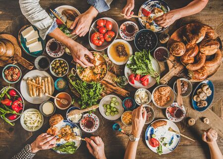 Turkish breakfast table. Flat-lay of peoples hands taking Turkish pastries, vegetables, greens, cheeses, fried eggs, jams and tea in copper pot and tulip glasses over wooden background, top view