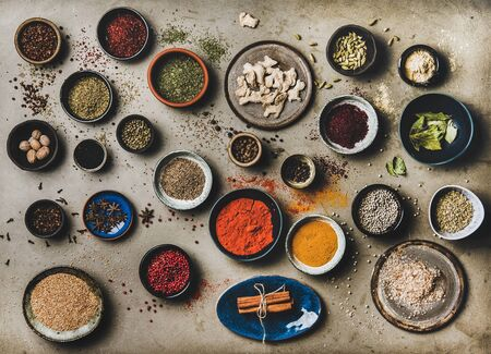 Flat-lay of spices in bowls and plates over grey background, top view. Black pepper, allspice, cloves, thyme, cumin, sesame, star anise, ginger, cinnamon, cardamom, mahlep, smoked salt, rosemary, bay