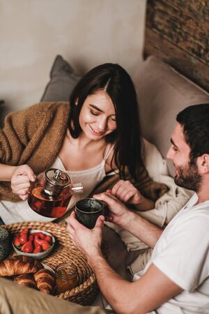 Young smiling happy couple in love in comfortable home clothing having breakfast in bed 写真素材
