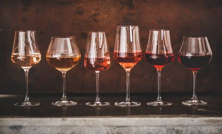 Various shades of Rose wine in stemmed glasses placed in line from light to dark colour on concrete table, rusty brown background behind. Wine bar, wine shop, wine tasting concept Standard-Bild